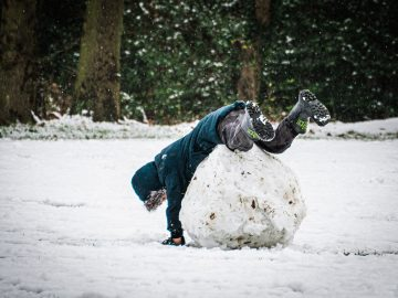 kid rolling a snowball